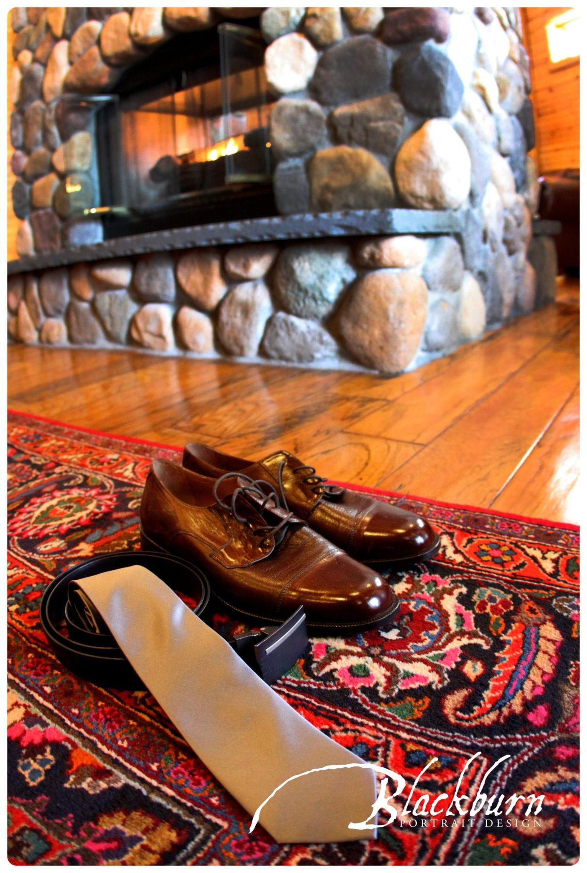Closeup of shoes, belt, and tie in front of fireplace