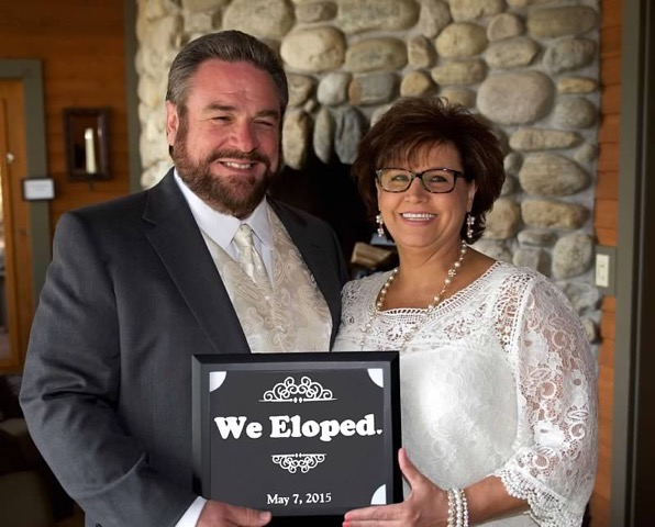 Bride and Groom pose with Elopement sign