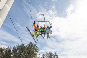 Skiers waving from the ski lift