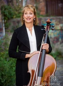 demetria, a cellist, standing with her cello