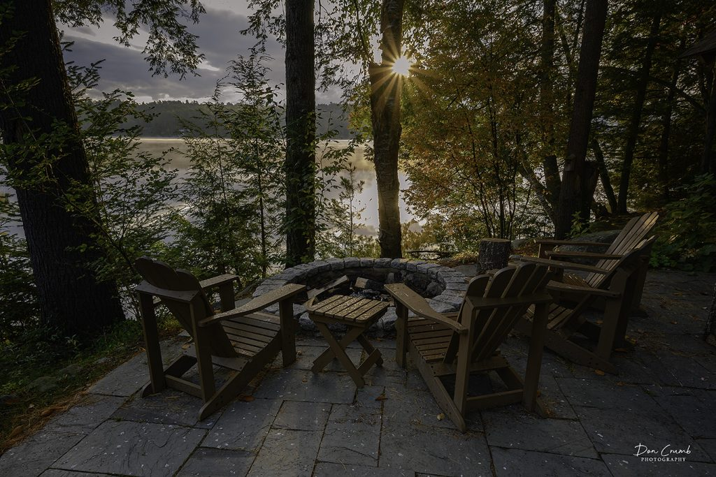 a firepit with adirondack chairs at the lakeside
